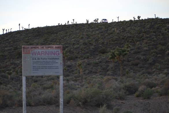 "Area 51 warning sign. A white security truck can be seen on the hill overlooking the sign. Are 51 security guards are often referred to as ""cammo dudes."" Credit: Alejandro Rojas"