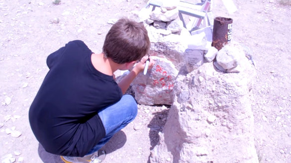 Hasvold's son signs a rock at what remains of the black mailbox. (Credit: Jeremiah Hasvold/YouTube)