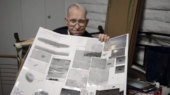 Bushman with a display of alleged UFO pictures from Area 51. (Credit: YouTube/Mark Q Patterson)