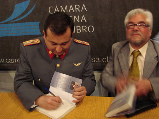 Capt. Rodrigo Bravo in uniform signing the book next to coauthor Juan Castillo. (image credit: Mario Valdes)