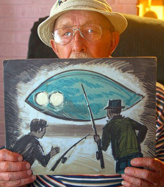 Charlie Hickson showing a painting of the 1973 Pascagoula abduction