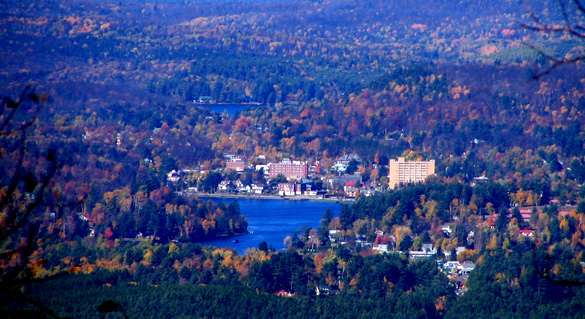 The sphere-shaped UFO moved directly overhead under 500 and appeared to be the size of a football stadium. Pictured: The village of Saranac Lake, with Lake Flower below and Lake Colby above, from Scarface Mountain to the southeast. (Credit: Wikimedia Commons)