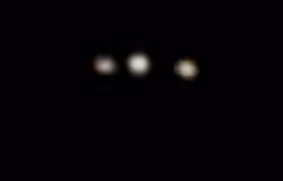 The lights appear to be attached to a triangle-shaped object. Pictured: Cropped and enlarged still frame from the witness video. (Credit: MUFON)