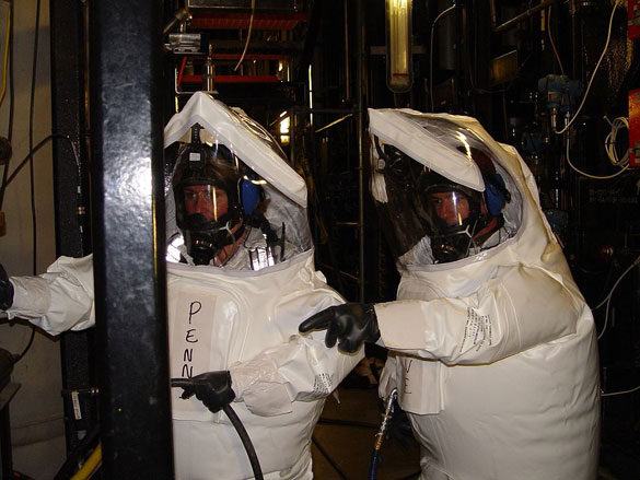 Two workers in demilitarization protective ensemble (DPE) performed maintenance work in an area of the Newport Chemical Agent Disposal Facility (NECDF) where chemical agent may have been present. (Credit: Wikimedia Commons)