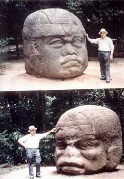 Sithin with giant Olmec statues in Mexico.