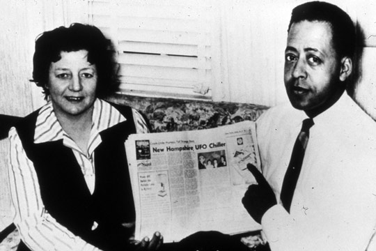 Betty and Barney Hill holding a newspaper featuring a story about their abduction experience.