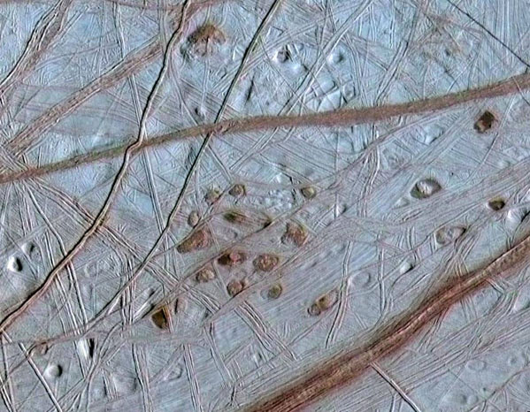 Reddish spots and hallow pits pepper the ridged surface of Jupiter's moon, Europa, in this view combining information from the images taken by NASA's Galileo spacecraft during two different orbits around Jupiter. (Credit: NASA)