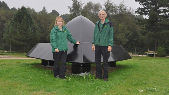 The Rendlesham UFO sculpture. Standing in front of it are artist Olivia English and Rendlesham Forest Recreation Manager Nigel Turner. (Credit: BBC)