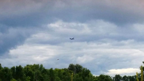 One of the witnesses snapped this still image which shows the military plane and a disc-shaped object. (Credit: MUFON)