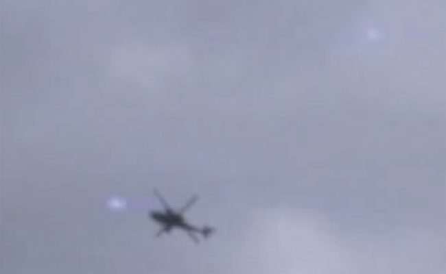 A still image taken from the video, showing a helicopter and multiple balls of light. (Credit: George Taylor/YouTube)